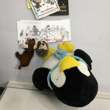 Three stuffed animals sitting in front of an open picture book
