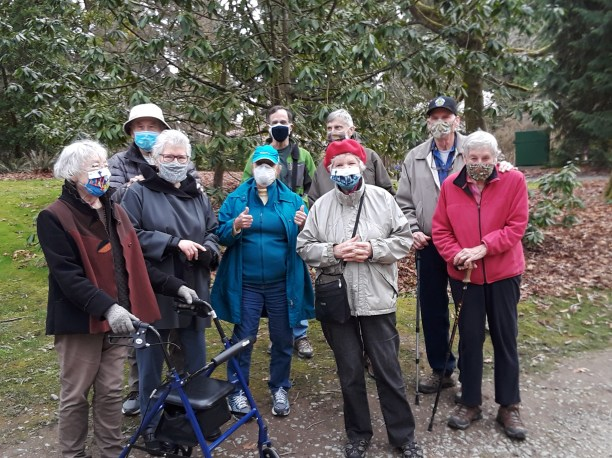 Members of the Stream of Light cluster, all wearing masks, in the Arboretum