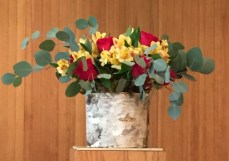 Flower arrangement with red and yellow flowers and eucalyptus leaves in birch bark container