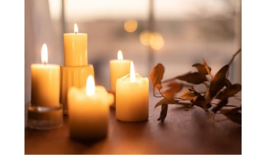 Still life of lit candles and dry leave on a vine
