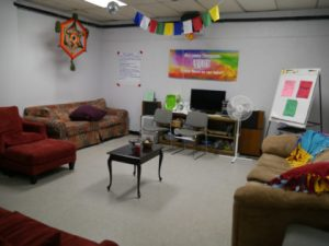 senior youth gathering room with couches, crafts and posters.
