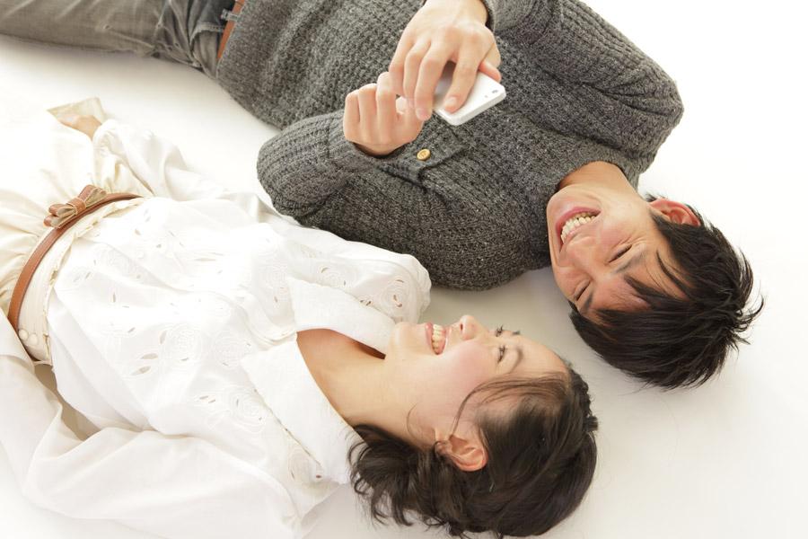 笑いながらスマホの画面を見ているカップル