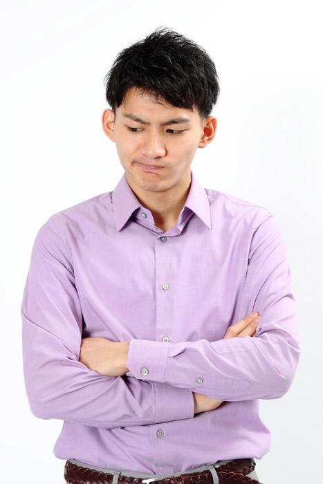 腕を組んで考え込んでいる日本人男性