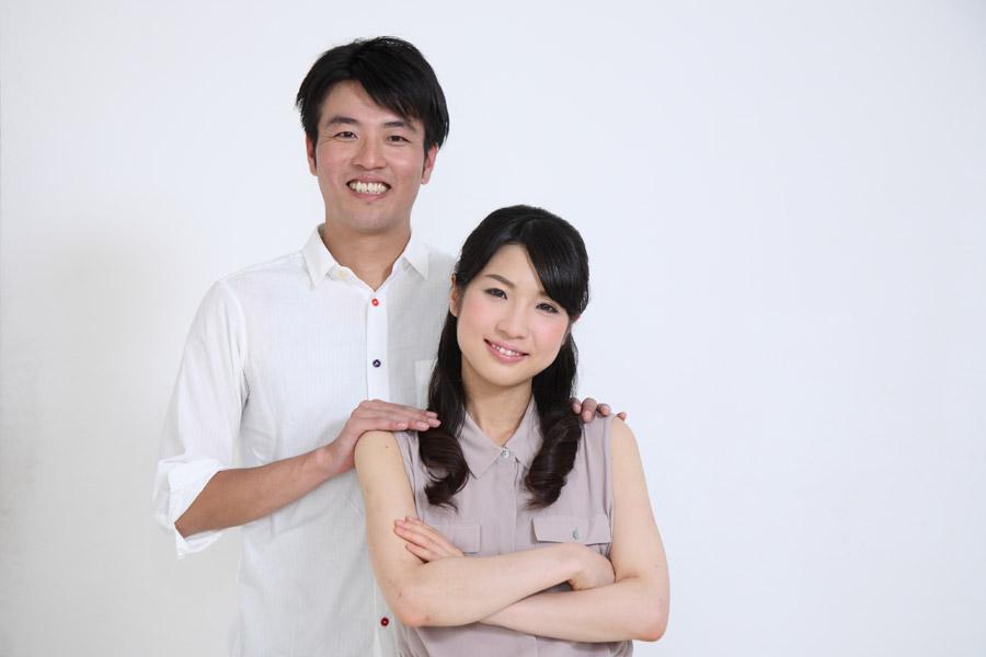 腕組みの妻の肩に手を置く夫