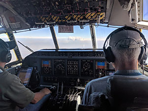 two people in plane cockpit, seen from behind