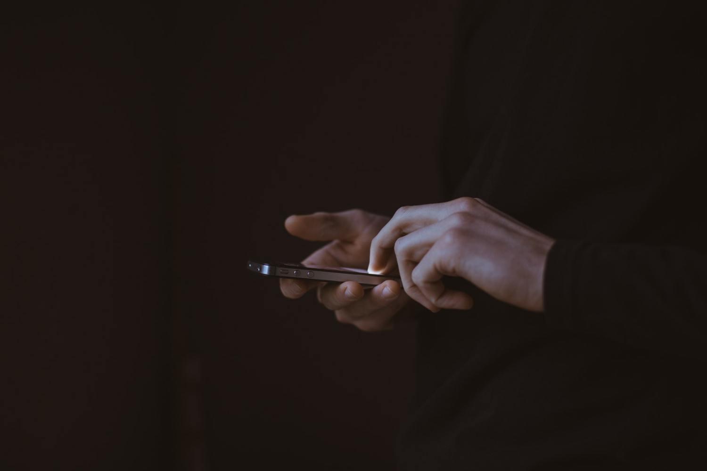 deux mains utilisant un iPhone