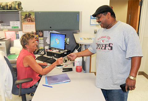 A man hands an ID card to a woman at a desk
