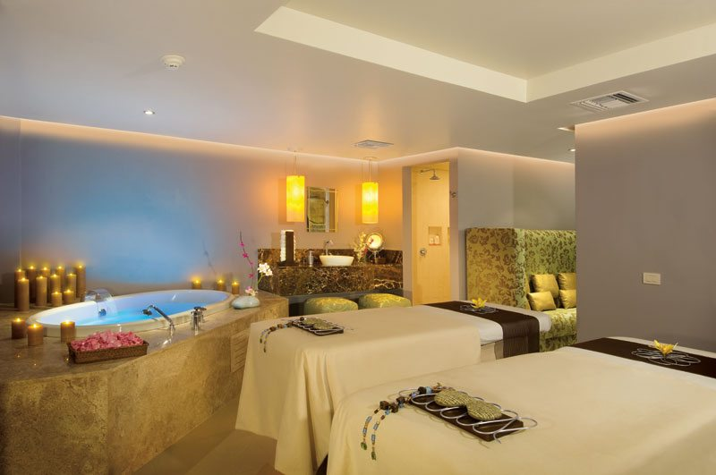 Indoor couple's massage suite including a luxurious hydrotherapy tub and beautiful décor.