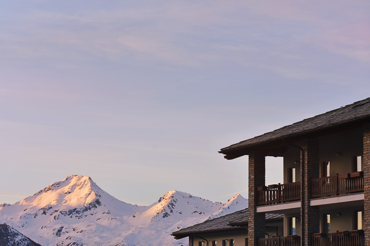 a wooden house with snowy mountains in the background