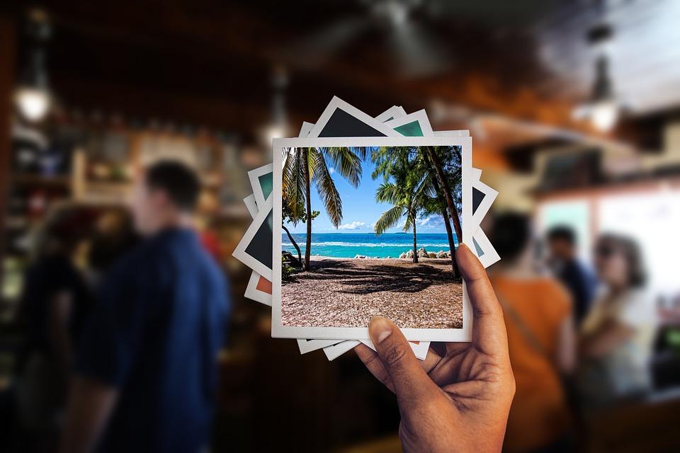 man holding travel photos