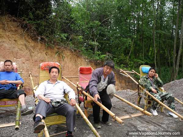 sedan chair rental stand hammock chinese chairs or litters being used to carry lazy tourists up a mountain
