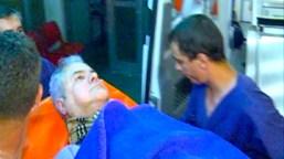 Adrian Năstase fraktes ut på båre. Såret etter streifkuddet i halsen er dekket av en bandasje og et lite Burberry-skjerf.