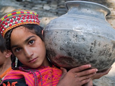 Traditional Kalasha girl carrying water in the Chitral region