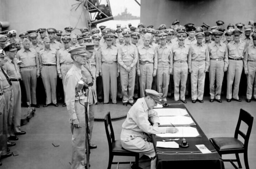General Douglas MacArthur signs as Supreme Allied Commander during formal surrender ceremonies on the USS MISSOURI in Tokyo Bay. Behind General MacArthur are Lieutenant General Jonathan Wainwright and Lieutenant General A. E. Percival.