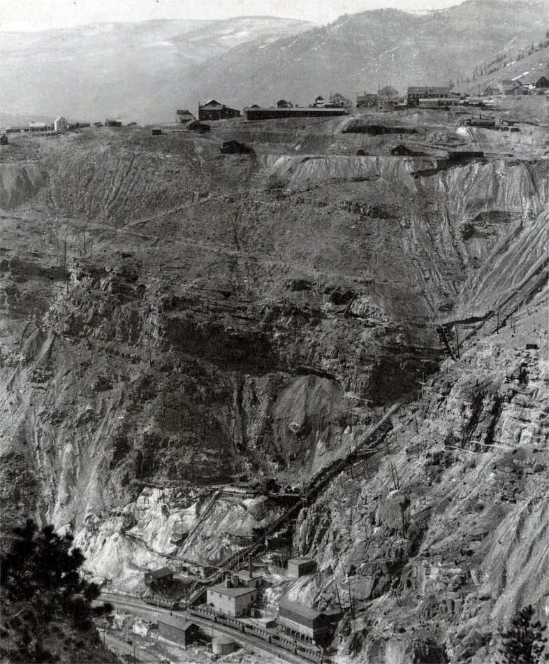 Photo postcard of Gilman with Belden at the bottom of the Eagle River Canyon. Ore cars are lined up on the tracks and the surface tram is clearly visible.