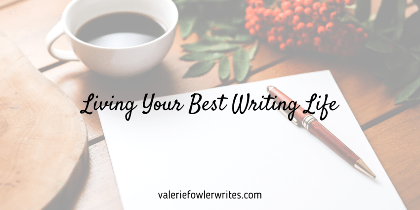 Pad of white paper and red pen next to a white mug and greenery with red berries on a wooden table.