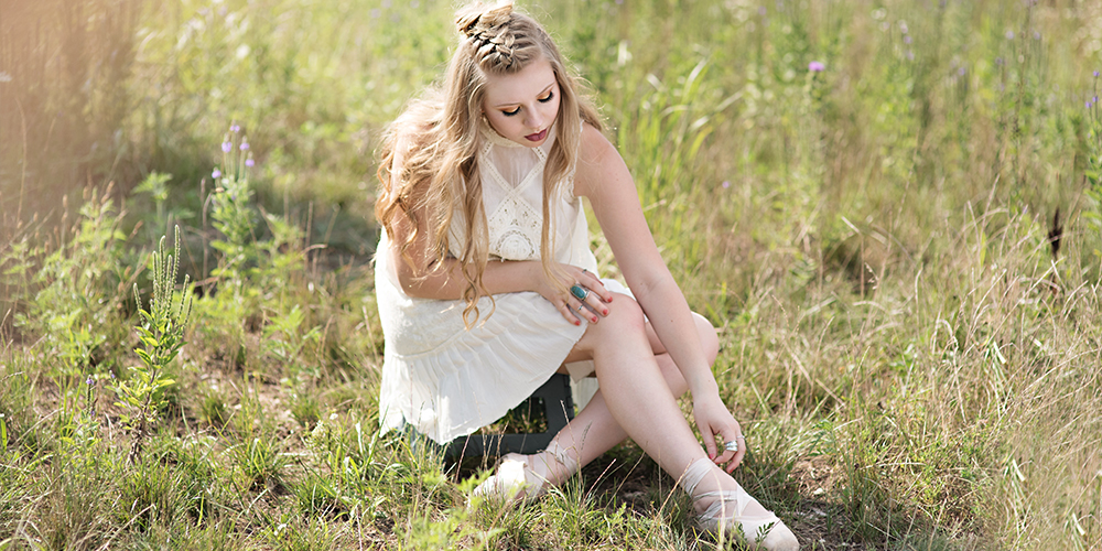 senior girl sitting in a field with ballet shoes