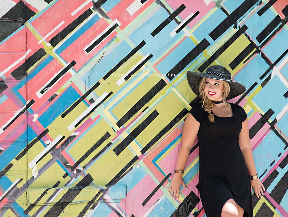 florida senior girl standing next to wall art in clearwater