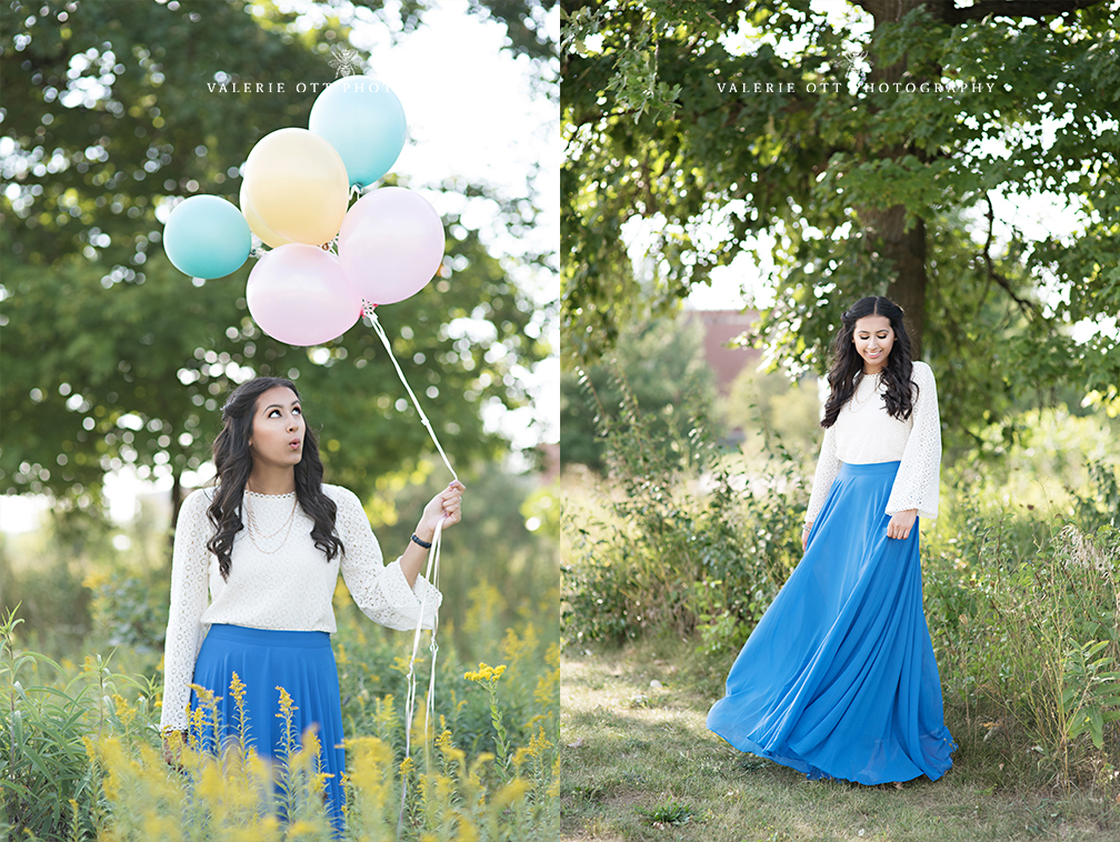 high school senior girl in a long blue skirt holding balloons in a park