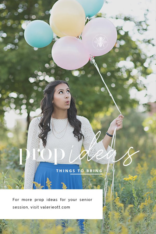 high school senior girl holding balloons standing in a field