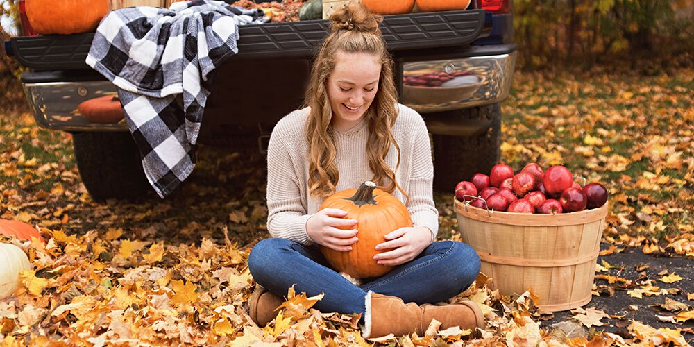 senior girl poses with pumpkin in fall