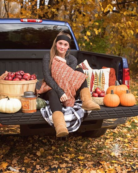 senior girl posing with pillows on truck in fall