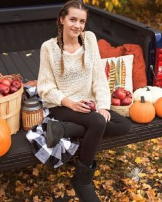 senior girl poses on truck with apple in fall