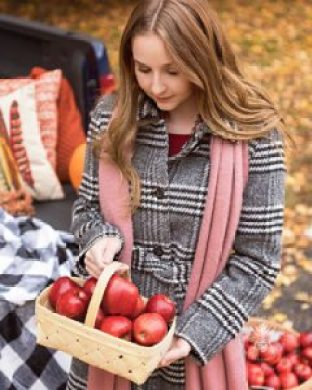 senior girl poses with apples in coat and scarf in fall location
