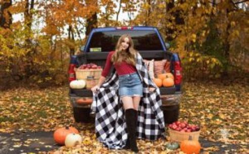 senior girl poses with checkered blanket in front of fall location with truck