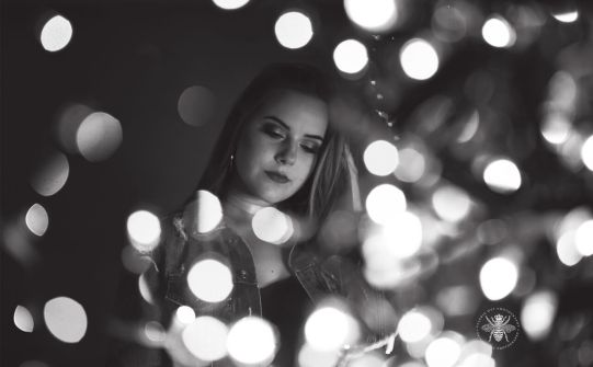 senior girl poses with lights