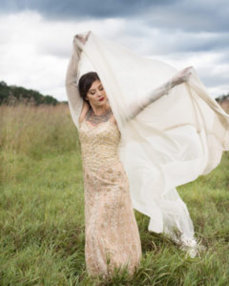 bride poses with wind blowing through her wedding veil in a field