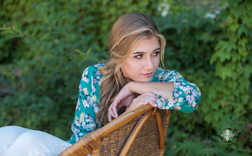 senior girl poses on chair wearing floral shawl and side ponytail