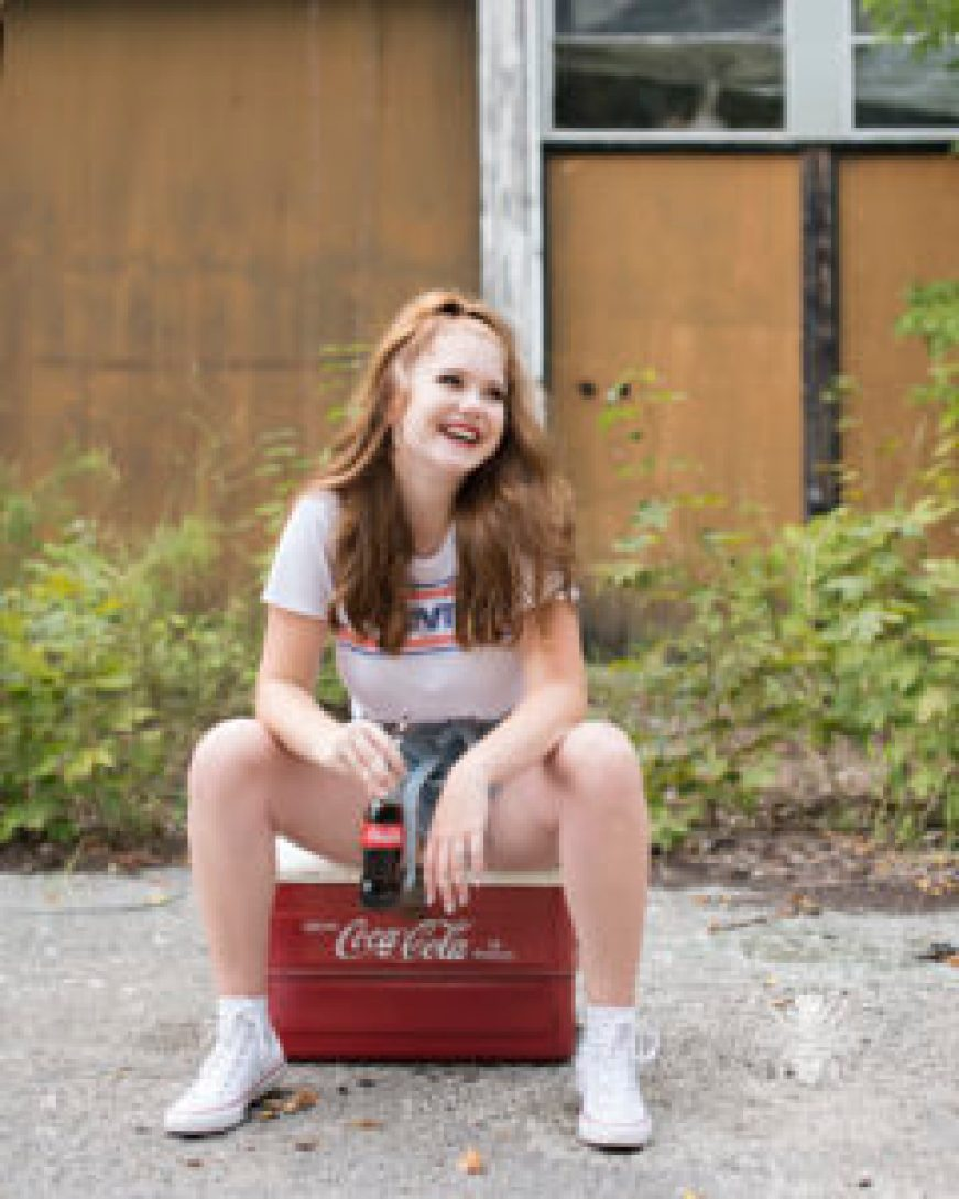 senior girl poses in vintage Levi's top, shorts, and sunglasses. She holds a vintage coke bottle.