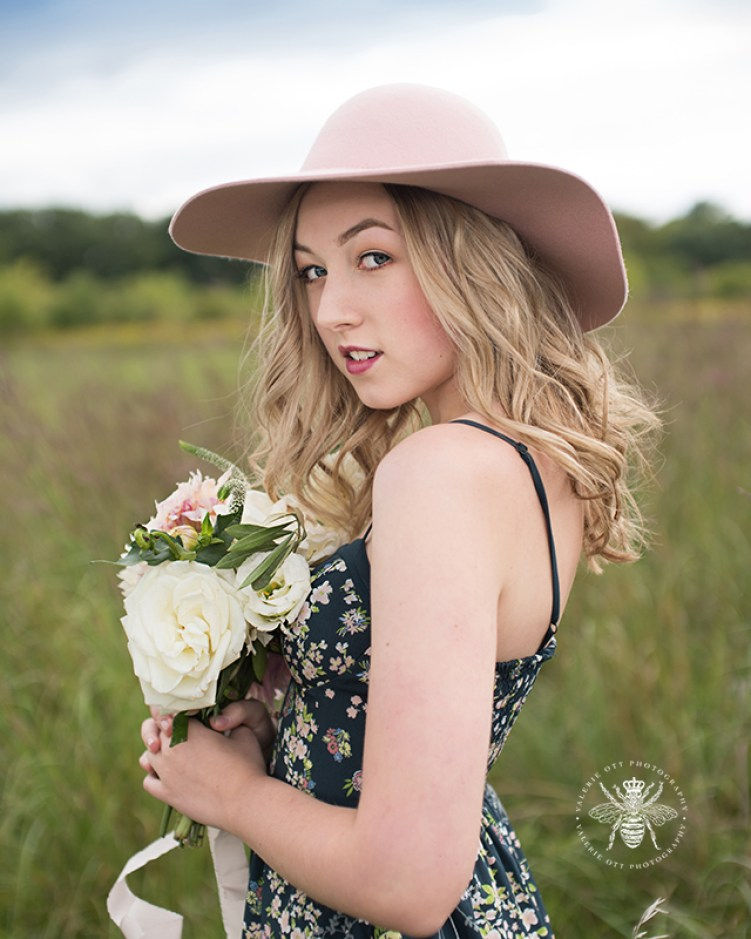 senior girl poses with flowers and sunhat in a field