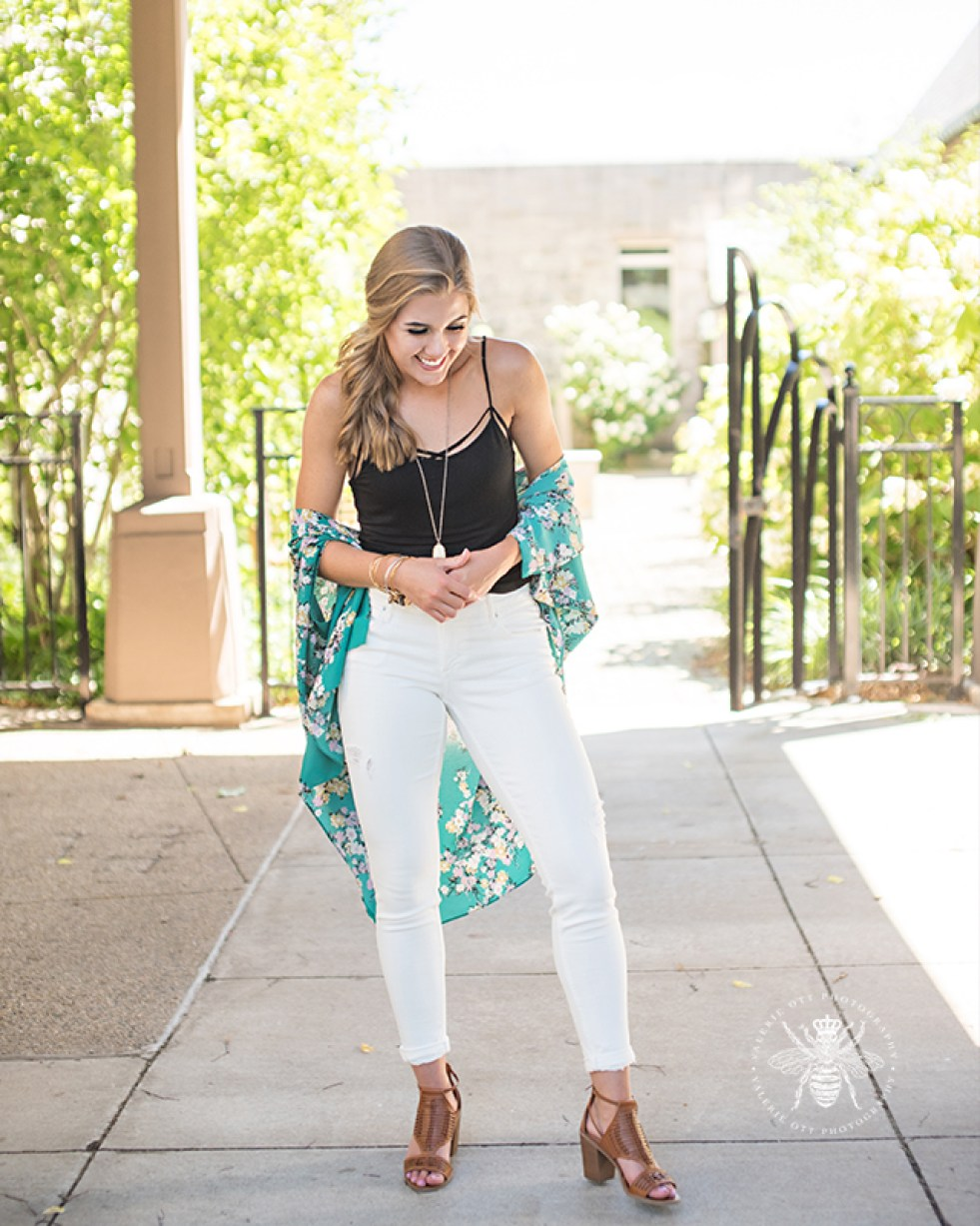 senior girl poses wearing green floral shawl, long necklace, black tank top, and white jeans