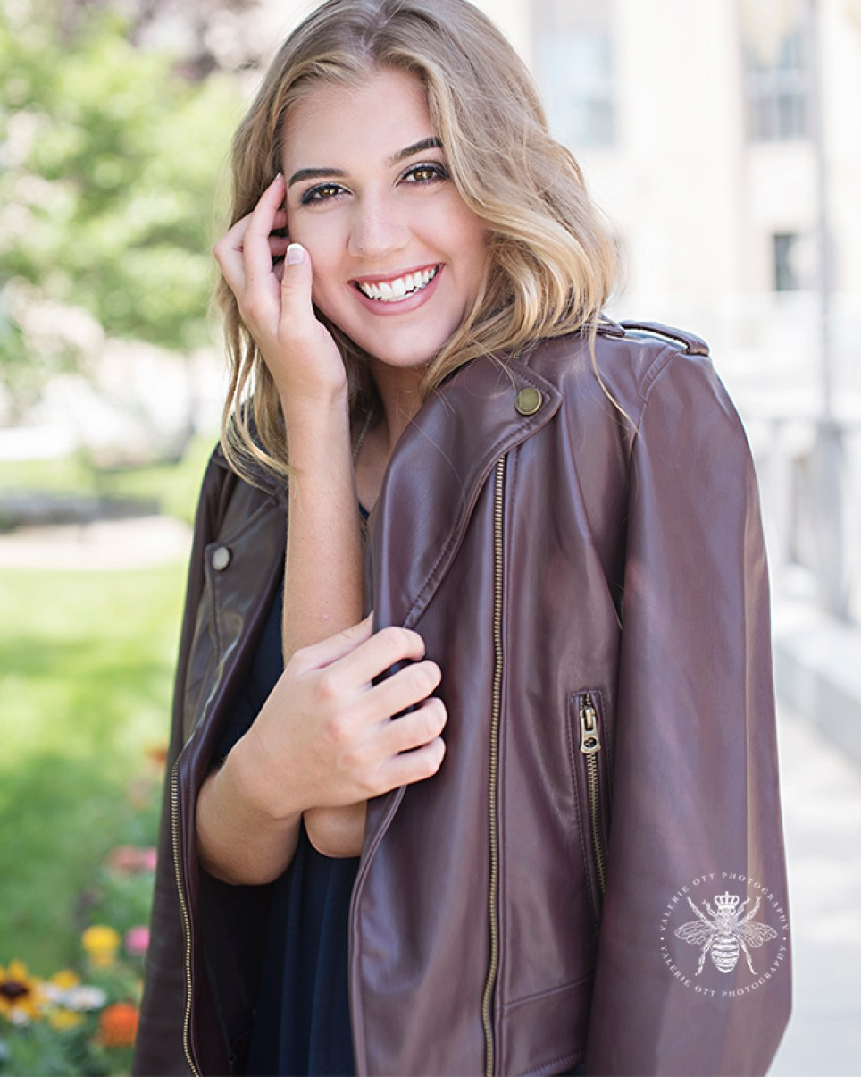 senior girl poses with brown leather jacket around her shoulders. Her true beauty shines through her smile.
