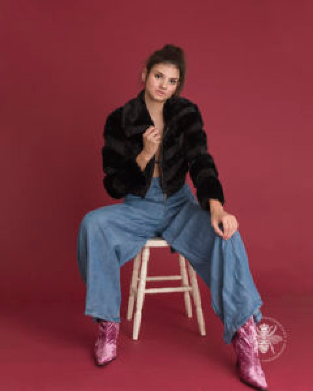 senior girl poses on a chair in front of a red background wearing a high fashion look. She wears a fur jacket, flowing oversized denim pants, and pink velvet boots