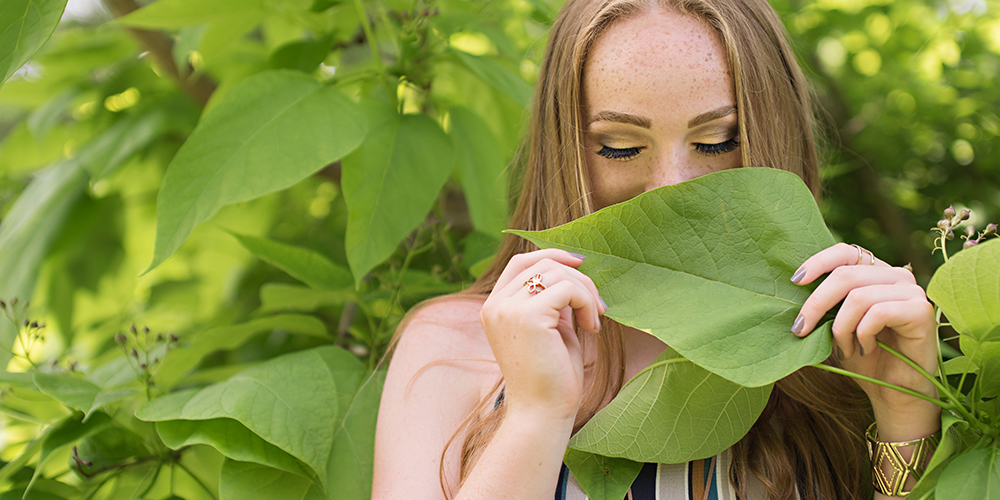 senior girl wears striped jumpsuit and poses with leaf in front of her face