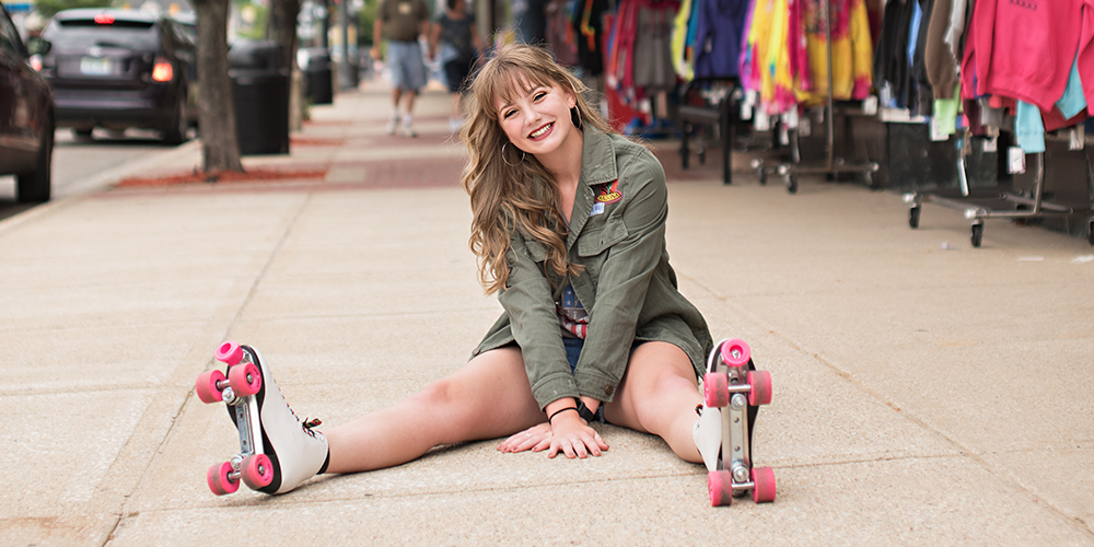 senior girl poses on rollerblades