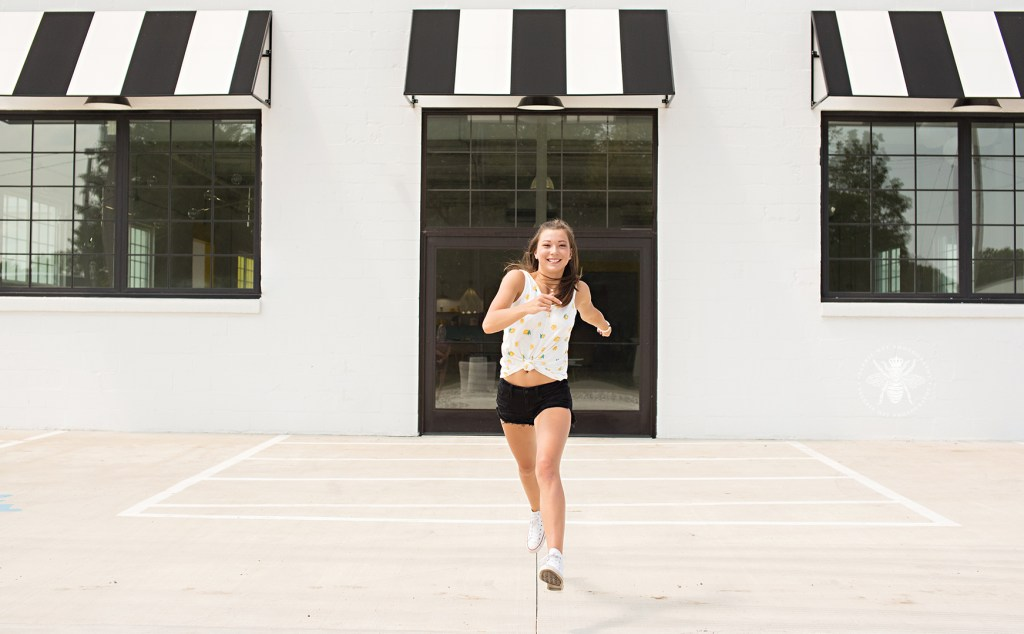 senior girl runs in front of building