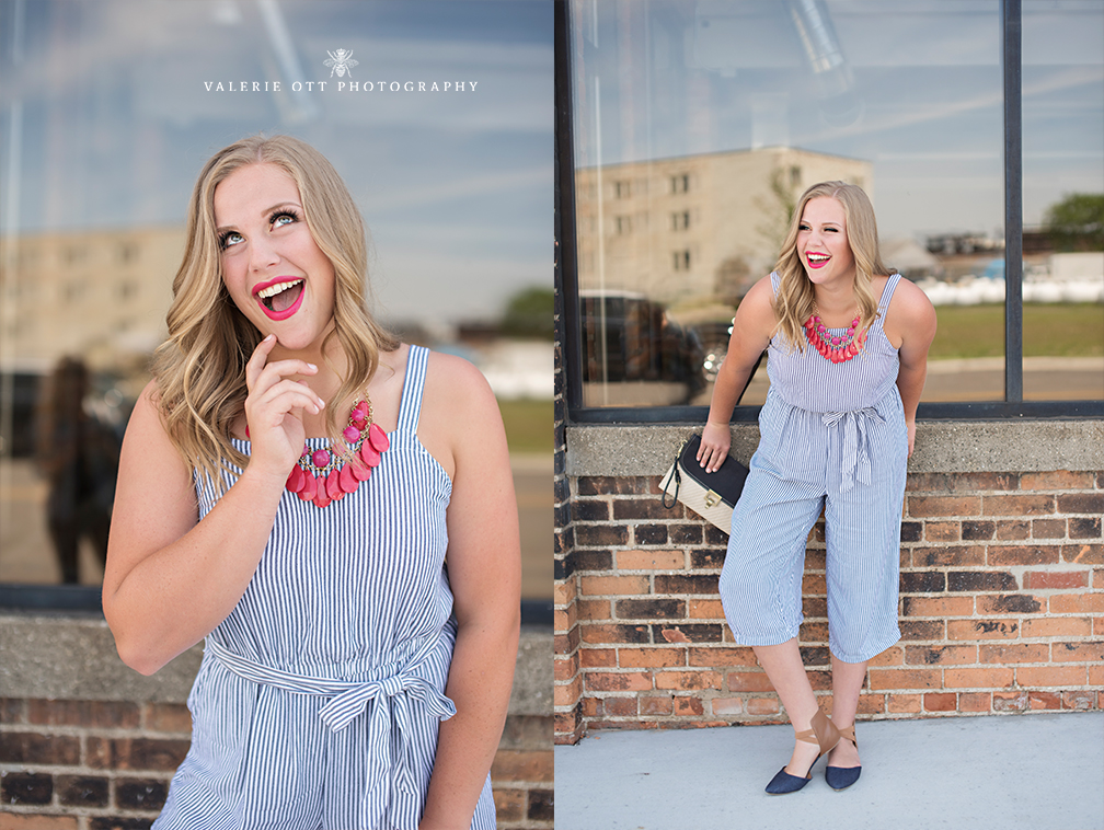 senior girl poses in blue striped jumpsuit and pink necklace with a matching pink lip. Her personality and true beauty is captured.