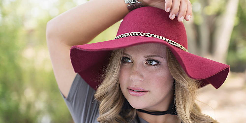 senior girl poses wearing red hat