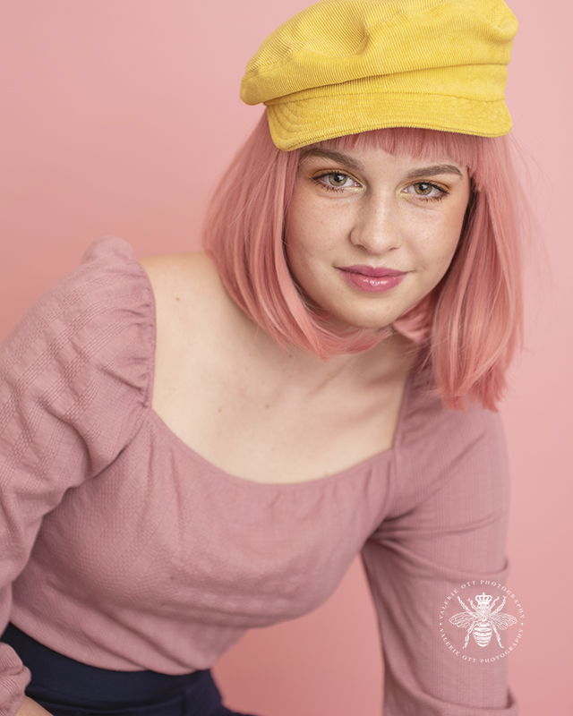 senior girl poses in front of pink background wearing a pink wig and a yellow hat