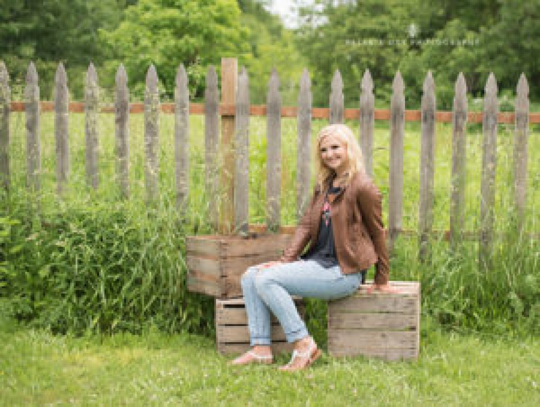 senior girl poses by vintage fence and wooden boxes wearing a brown leather jacket