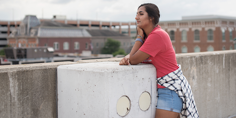 senior girl poses in red top on top of parking garage