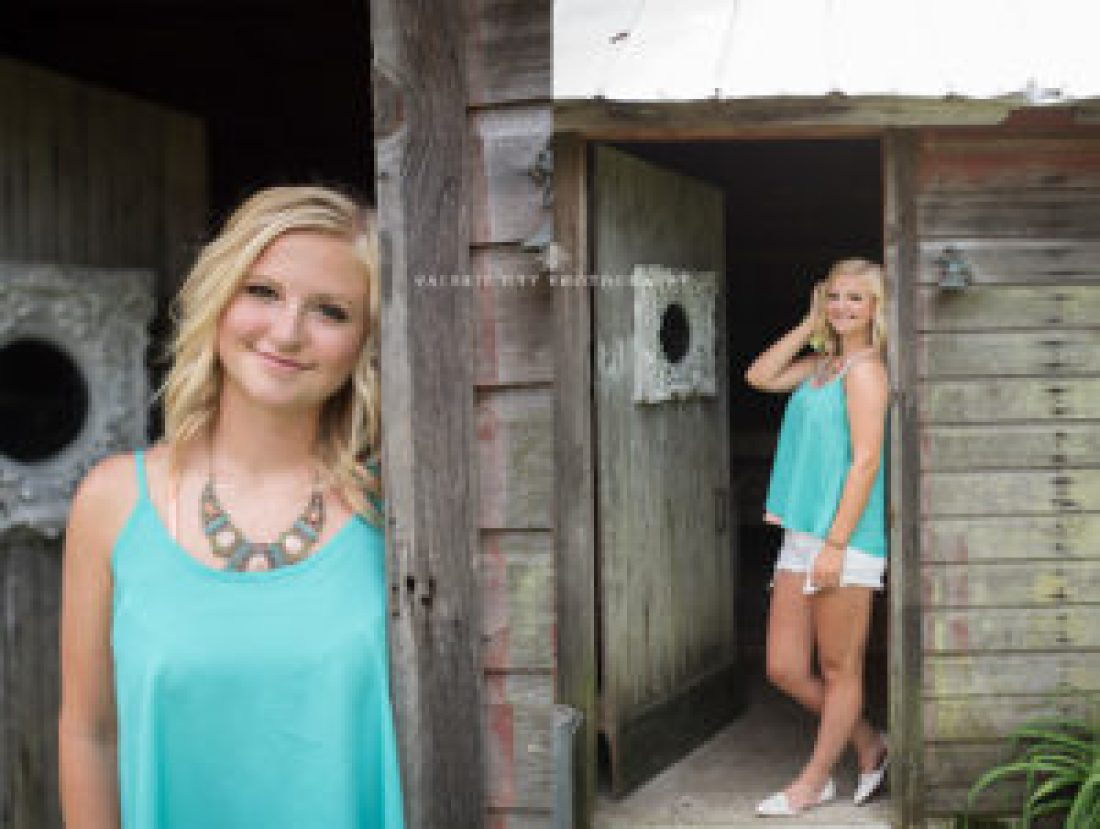senior girl poses in vintage location wearing a blue top