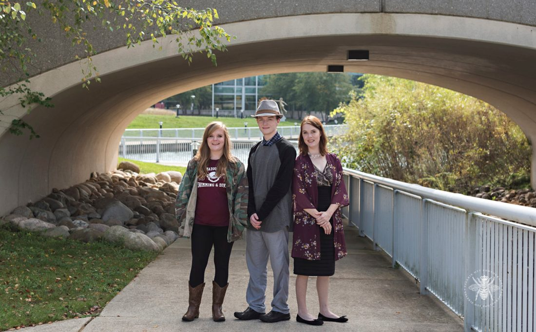 triplets pose under bridge together, two girls and boy in middle