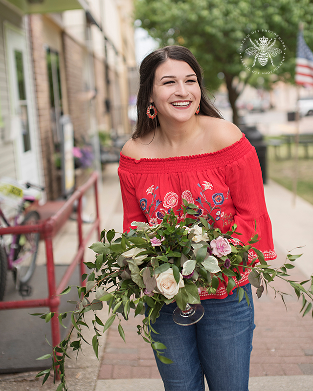 senior girl wears red off the shoulder top and poses with a bouquet of flowers