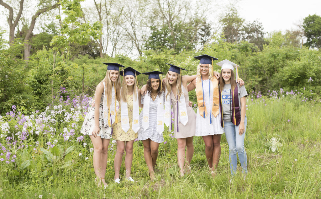 West Michigan high school graduates pose in a field wearing their cords for and caps for a cap and gown session.