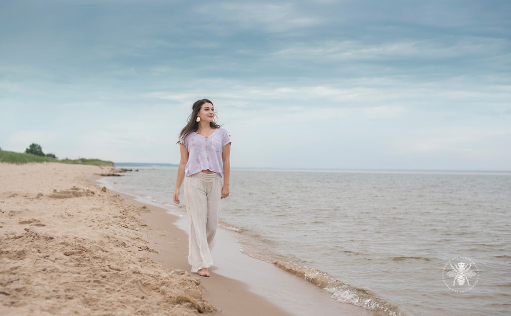 senior girl wears flowing pants and top and strolls along the beach